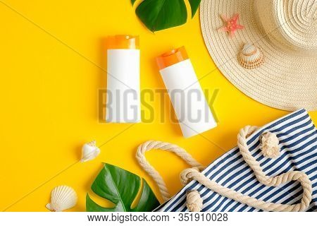 Suntan Or Sunblock Lotions Packages On Yellow Background With Beach Bag, Female Summer Hat, Green Tr