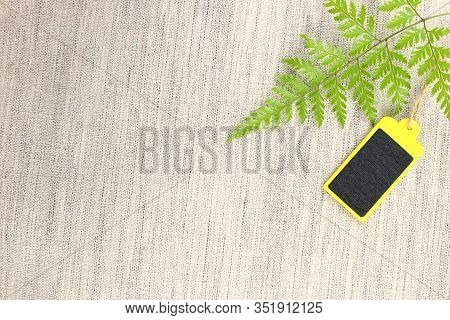 Yellow And Black Blank Wooden Tag With Leaves On Fabric
