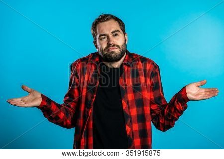 Young Handsome Unsure Guy In Red Plaid Shirt Shrugs His Arms, Makes Gesture Of I Dont Know, Cant Hel