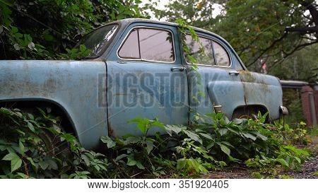 Abandoned Rusty Car In Junkyard. Forgotten Discarded Rusty Old Blue Car In Scrapyard