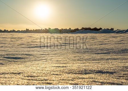 Snow-covered Field With Hummocks, The Sun Setting Over The Horizon On A Winter Evening