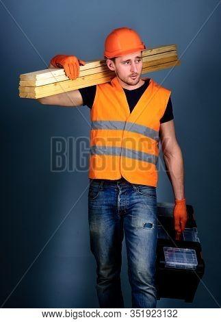 Carpenter, Woodworker, Labourer, Builder On Busy Face Carries Wooden Beams On Shoulder. Construction
