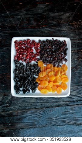 Dried Fruits On A Dark Wooden Background.raisins, Dried Apricots, Prunes, Dried Cherries On A Square