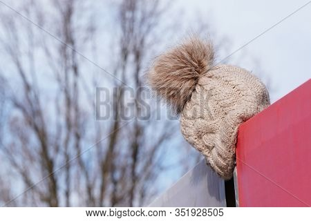 The Light Knitted Hat Was Lost Or Forgotten And Hung Over The Fence. Warehouse Lost And Found, Lost