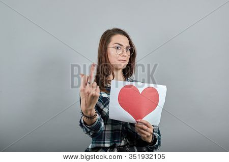 Young Brunette Girl Blue Green In Checked Shirt On Grey Background Angry Woman Holds Piece Of Paper