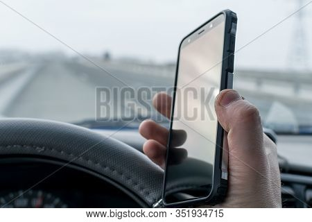 In The Hand Of The Driver Of The Car, A Cell Mobile Phone That He Uses While Driving On The Speed Hi