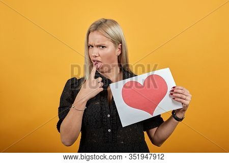 Young Blonde Girl In Black Dress On Yellow Background Angry Woman Holds Piece Of Paper With Red Hear