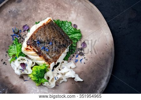 Gourmet fried European skrei cod fish filet with rapini broccoli rabe and noodles as top view on a modern design plate with copy space right