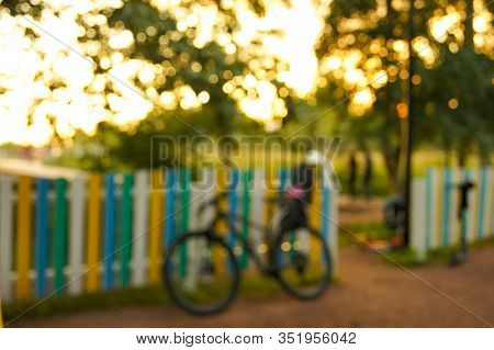 Blurred Defocus Bicycle Standing Under A Wooden Colourful Fence At Sunset Bokeh