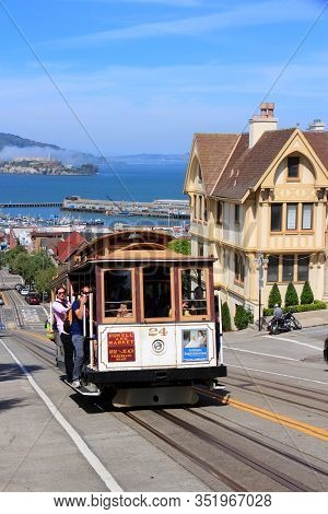 San Francisco, Usa - April 8, 2014: People Ride The Historic Cable Car With Alcatraz Island In Backg