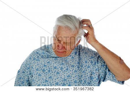 Man with an Itch. A man in a Hospital Exam Gown scratches an itch on his head. Isolated on white. Room for text. Clipping Path. People who have itches often try to scratch them or see a doctor.
