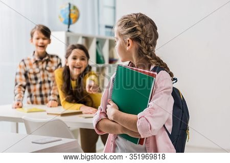 Selective Focus Of Bullied Schoolgirl Holding Notebooks Near Cruel Schoolkids