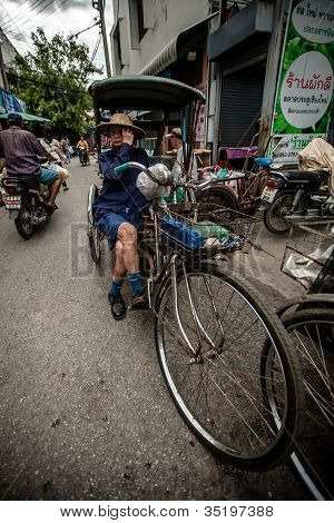 Tricycle (Sam Law) driver having food in his tricycle