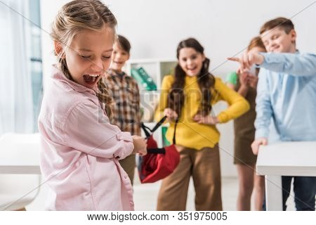 Selective Focus Of Bullied Schoolgirl Screaming Near Cruel Cruel Pupils Holding Backpack And Pointin