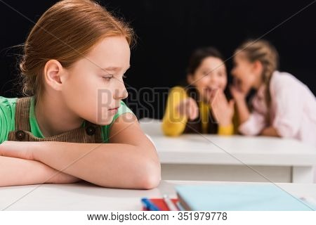 Selective Focus Of Upset Schoolkid Sitting Near Classmates Laughing And Gossiping In Classroom Isola