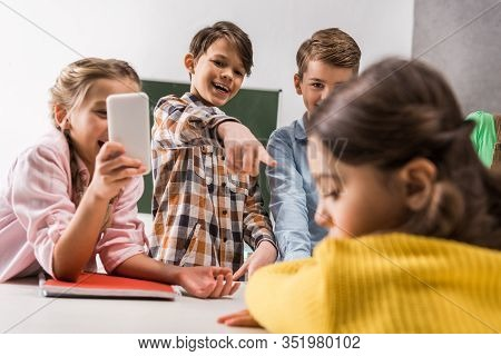 Selective Focus Of Schoolkid With Smartphone And Cruel Classmates Laughing Near Bullied Kid, Cyberbu