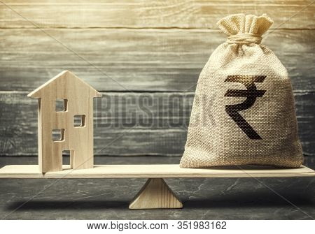 Money Bag With Indian Rupee And Wooden House On Scales. Fair Value Of Real Estate And Housing. Payme