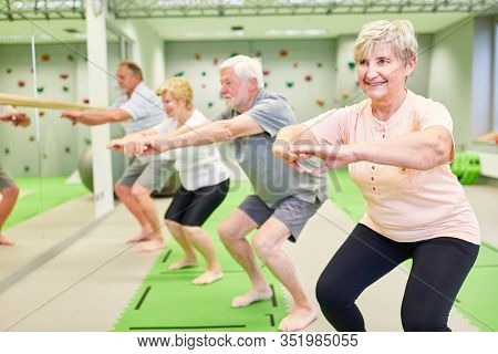 Seniors do squats in the fitness class for strength and motor skills and fall prophylaxis