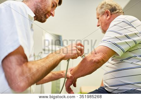 Doctor makes an ultrasound therapy on the elbow as a pain therapy in a senior patient