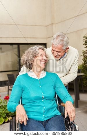 Senior woman in wheelchair with husband in rehab clinic or senior residence