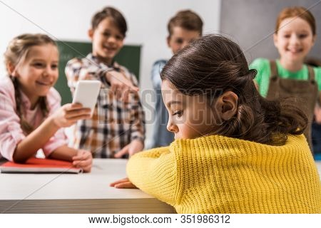Selective Focus Of Bullied Schoolgirl Sitting Near Schoolkid With Smartphone And Cruel Classmates, C