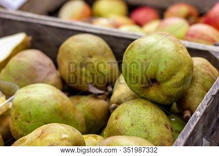 A Portrait Of A Wooden Crate Full Of Pears At A Local Market. In The Background There Are Blurred Ap