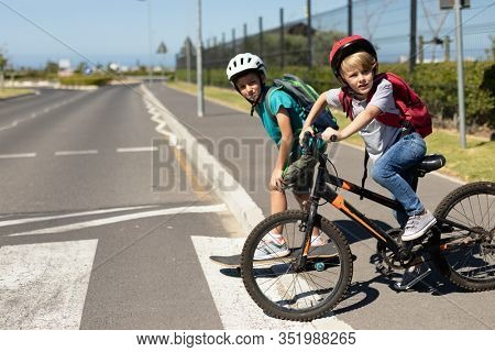 Side view of two Caucasian school boys wearing cycling helmets looking for traffic and waiting on a pedestrian crossing to cross the road, one on a skateboard and one riding a bicycle, on their way to