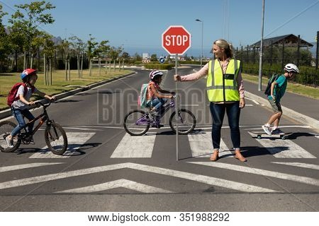 Front view of a blonde Caucasian woman wearing a high visibility vest and holding a stop sign, standing in the road, turning to the side while three schoolchildren ride bicycles and a skateboard on a