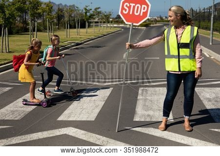 Front view of a blonde Caucasian woman wearing a high visibility vest and holding a stop sign, standing in the road, turning to face two schoolgirls riding scooters on a pedestrian crossing, stopping