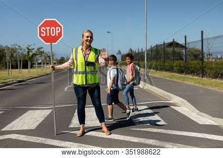 Front view of a blonde Caucasian woman wearing a high visibility vest and holding a stop sign, standing in the road and stopping traffic on a pedestrian crossing, while two schoolchildren cross the