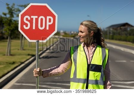 Front view close up of a blonde Caucasian woman wearing a high visibility vest and holding a stop sign, standing in the road and looking to the side on a pedestrian crossing, waiting to help children