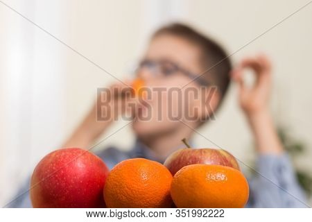Mandarins And Apples In The Foreground. In The Background A Boy Who Eats Fruit With Taste.