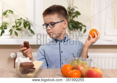 Chocolate Bar Or Tangerine Fruit. School-age Boy Sits At The Table And Wonders What To Choose.