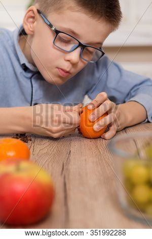 The Boy With Glasses Picks Cloves Into The Mandarin Fruit. Garnishing The Tangerine Fruit With Clove