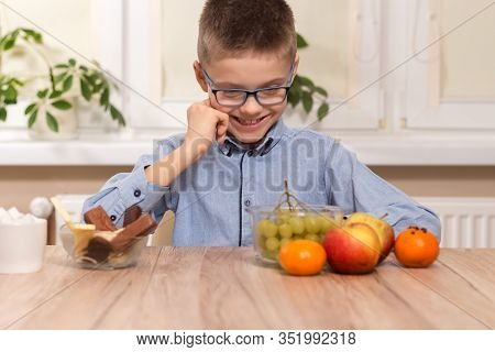A School-age Boy Sits At A Table And Stares At The Fruit Lying On The Table With A Smile. The Boy St