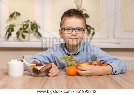 Smiling School-age Boy Sits At A Table And Brings Fruits To Him. With The Other Hand, He Moves The S