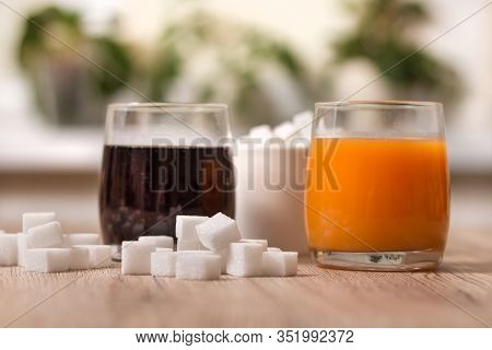 Sugar Cubes Are Scattered On The Kitchen Counter. There Is Cola In One Glass And Juice In The Other.