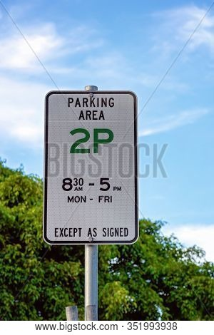 A Parking Sign On A Steel Post Indicating Hours Cars Can Be Parked In Parkland
