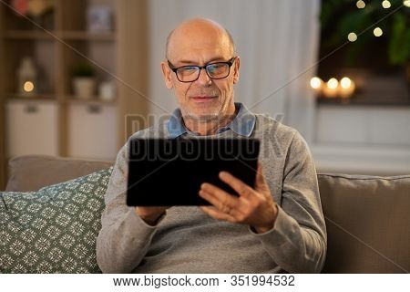 technology, old age and people concept - happy bald senior man with tablet pc computer sitting on sofa at home in evening