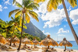 Caribbean Beach With Palms And Straw Umrellas On The Shore With Gros Piton Mountain In The Backgroun