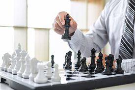 Black And White Chess With Player, Hands Of Businessman Thinking To Moving Chess Figure In Competiti