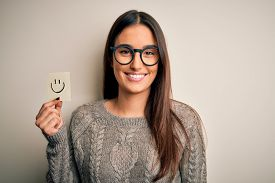 Young beautiful brunette woman wearing glasses holding paper with smile emoji with a happy face standing and smiling with a confident smile showing teeth