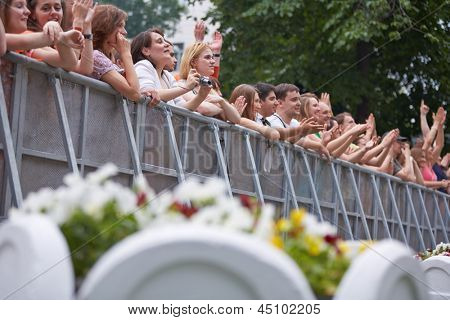 MOSCOW - JUN 23: People stand and applaud at fence at concert of Chaif rock-band during VII traditional festival of live sound Music of Summer in Hermitage Garden, Jun 23, 2012, Moscow, Russia.