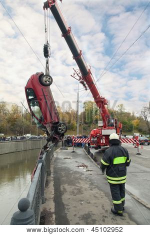 MOSCOW - OCT 9: Peugeot 206 suffered in the river Yauza and large red rescue vehicle helps injured in car crash on October 9, 2011 in Moscow, Russia.