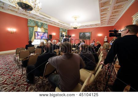 MOSCOW - APRIL 24: Newspapermans sit in front of TV on Enlarged meeting of Council in Red Hall of Guest extension in Grand Kremlin Palace on April 24, 2012 in Moscow, Russia.