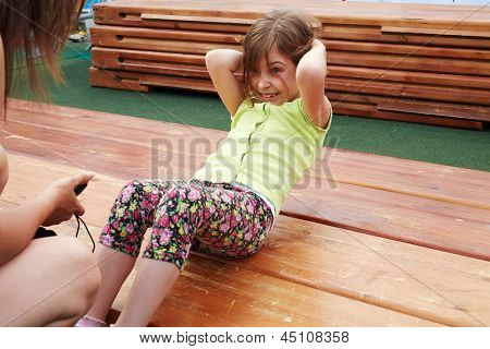 Little girl makes abdominal crunches for limited time on wooden platform poster