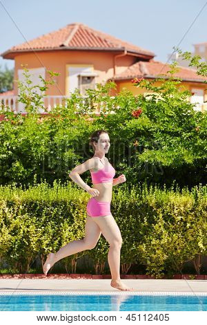Young smling woman in pink sportswear runs along poolside