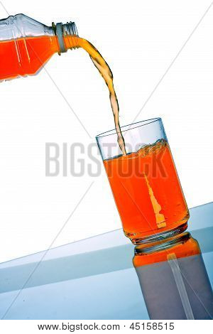 Orange Drink Pouring In Glass From Plastic Bottle