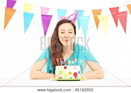 A smiling birthday female with a party hat blowing the candles on her birthday cake isolated against white background