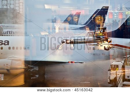 Worker Deices The Wing Of The Plain In Frankfurt Airport